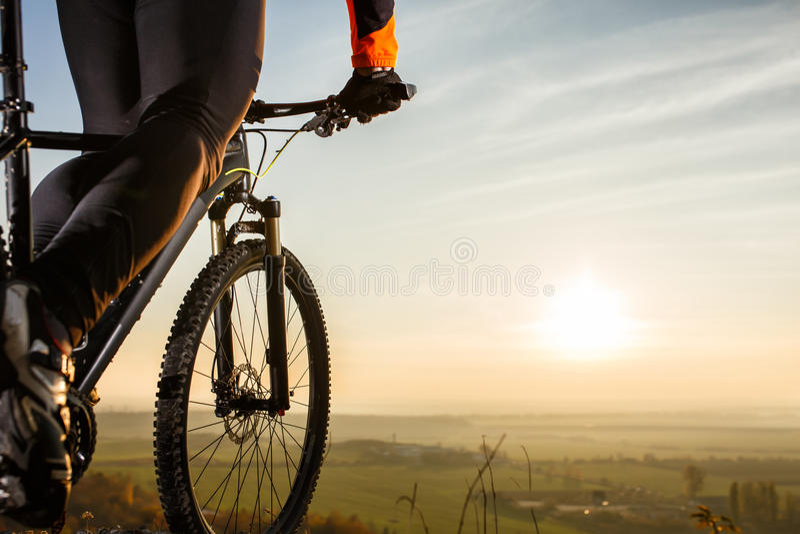 Närbildsikt på en cyklistcyklist som underifrån rider en cykel på vägsikten på en bakgrund av soluppgång royaltyfri fotografi