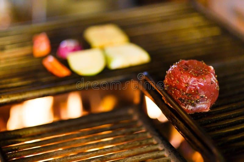 Närbildsikten av det kryddade rå köttet som förläggas på fyrpannan med brinnande trä i restaurangköket arkivbild
