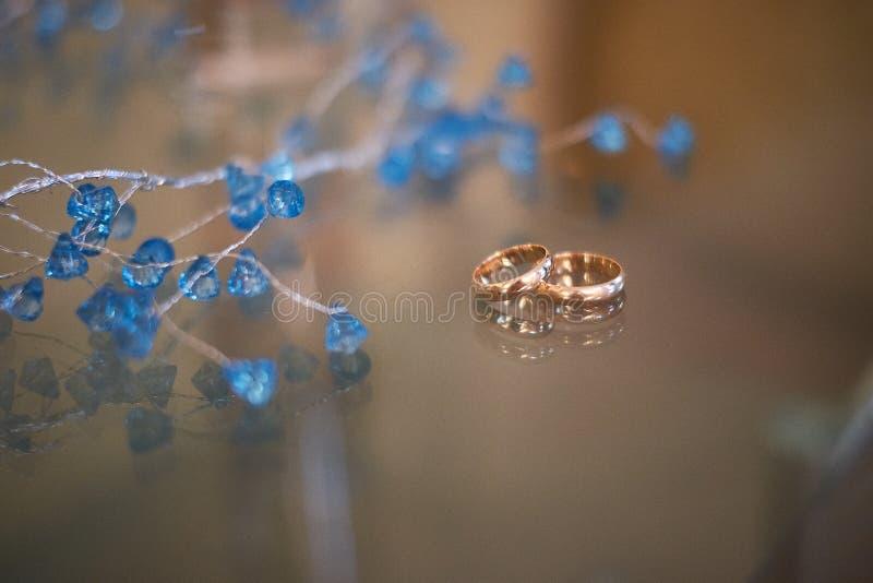 Närbildsikten av guldbröllopcirklar och härliga små blått blommar royaltyfri bild