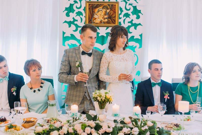 Närbildsikten av nygifta personerna och deras vänner som lyssnar till rostade brödet i restaurangen royaltyfri foto