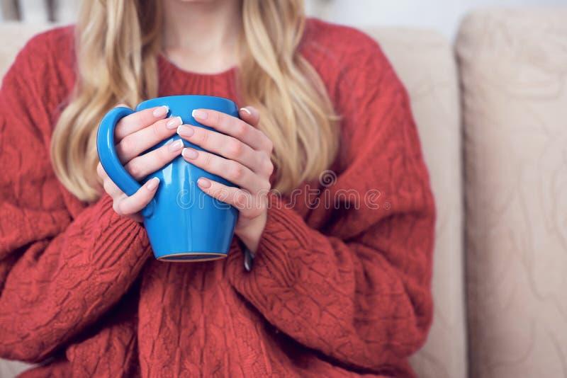 Närbildsikten av unga flickan värme händer på en kopp te eller ett kaffe i ett kallt lägenhetsammanträde på soffan Problem av royaltyfri fotografi