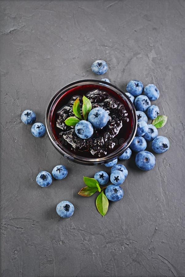 Närbildsiktsdriftstopp i den glass bunken med det nya mogna blåbäret och sidor royaltyfria bilder