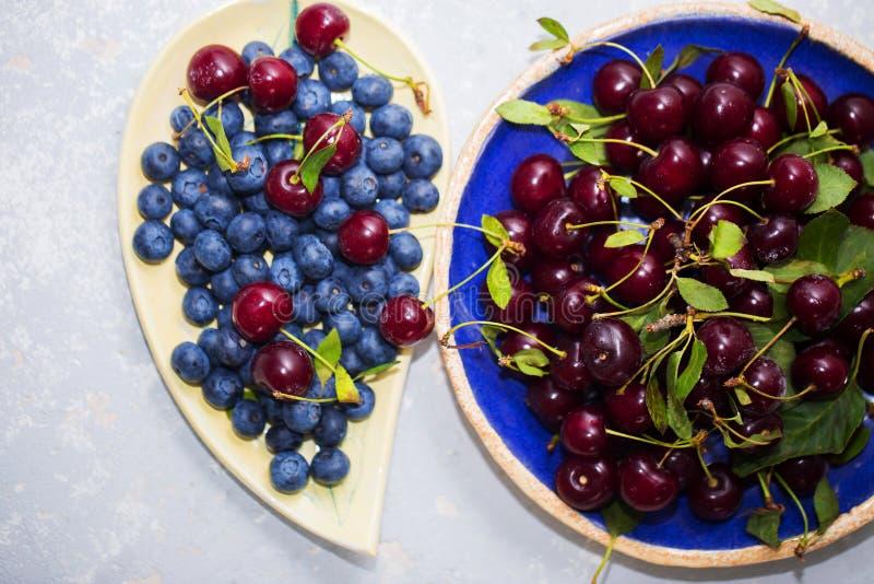 Närbildskott av körsbäret och blåbär i bunkar royaltyfria foton