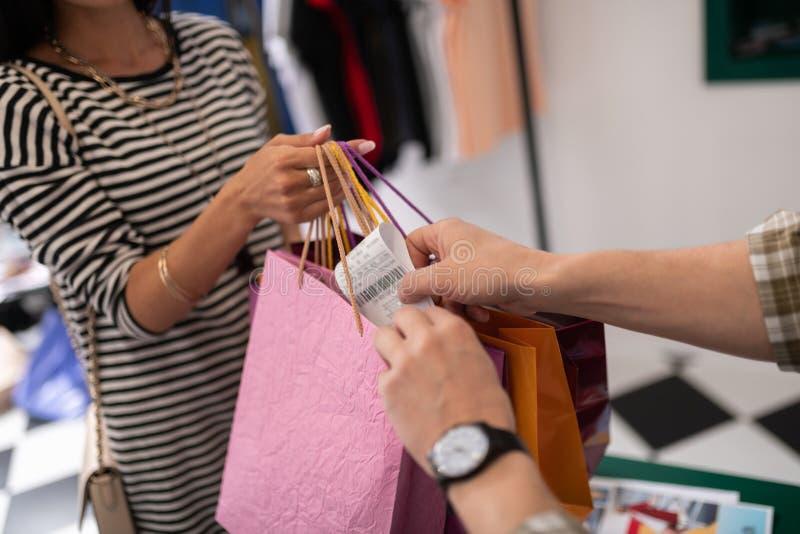 Närbildskott av kassörskan som sätter ett kvitto till den shoppa packen royaltyfria foton