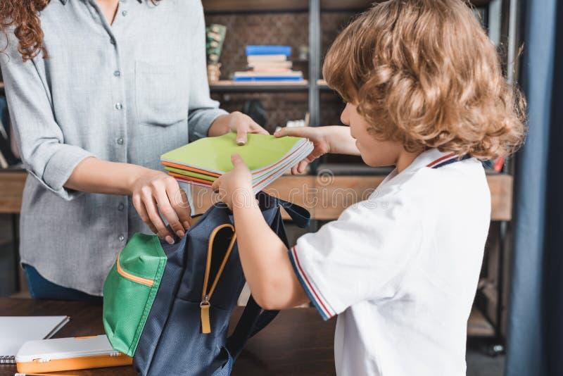 närbildskott av modern och den förtjusande sonen som förbereder ryggsäcken fotografering för bildbyråer