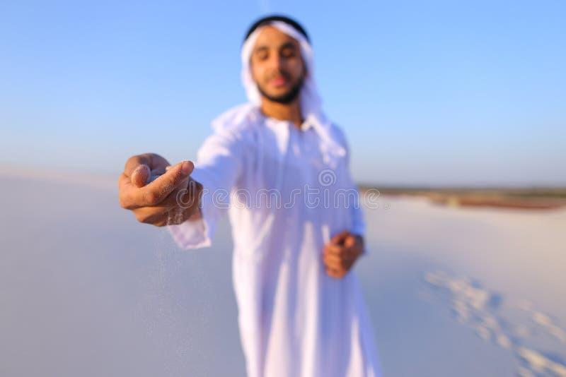 Närbildskott av ståenden och händer av den unga arabiska grabben i sandigt D arkivbild