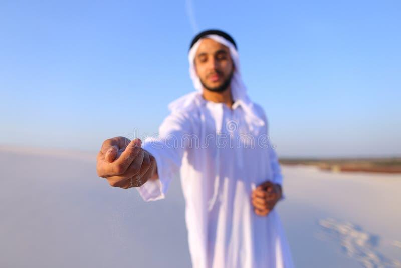 Närbildskott av ståenden och händer av den unga arabiska grabben i sandigt D royaltyfri foto