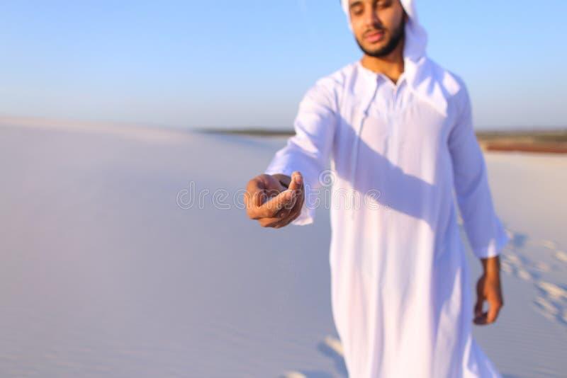 Närbildskott av ståenden och händer av den unga arabiska grabben i sandigt D arkivfoto