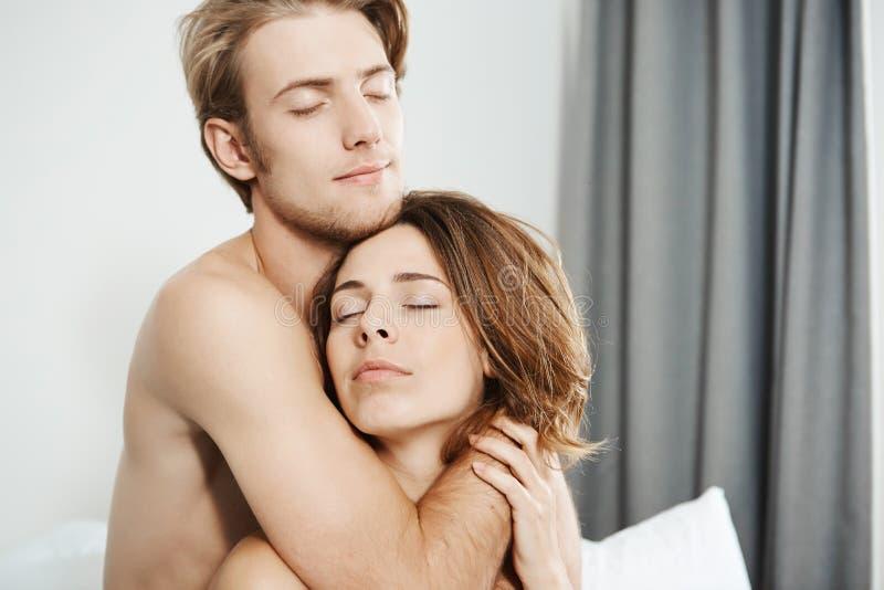 Närbildskott av två förälskade som härliga mjuka unga vuxna människor kramar i säng med stängda ögon och romantiskt leende Par royaltyfri foto