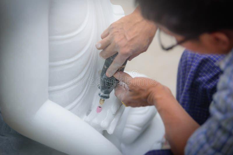 Närbildskulptörer som använder den elektriska drillborren på en marmor för att snida arkivfoton