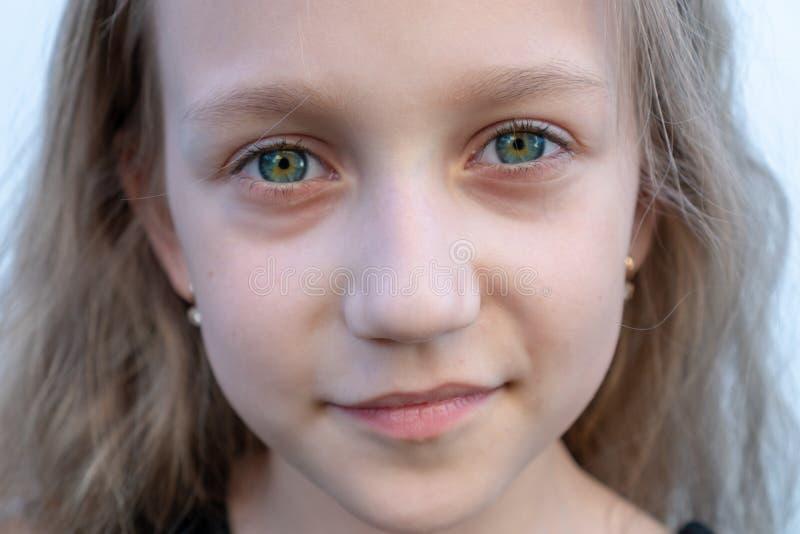 Närbildsommarstående av unga flickan 8 år gammal unge som ler, blåa gröna ögon royaltyfri foto