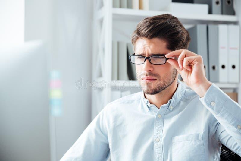 Närbildstående av affärsmannen i glasögon som ser bildskärmen arkivbild