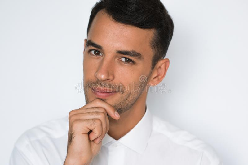 Närbildstående av att le den stiliga handen för ung man på hakan som poserar på vit bakgrund fotografering för bildbyråer