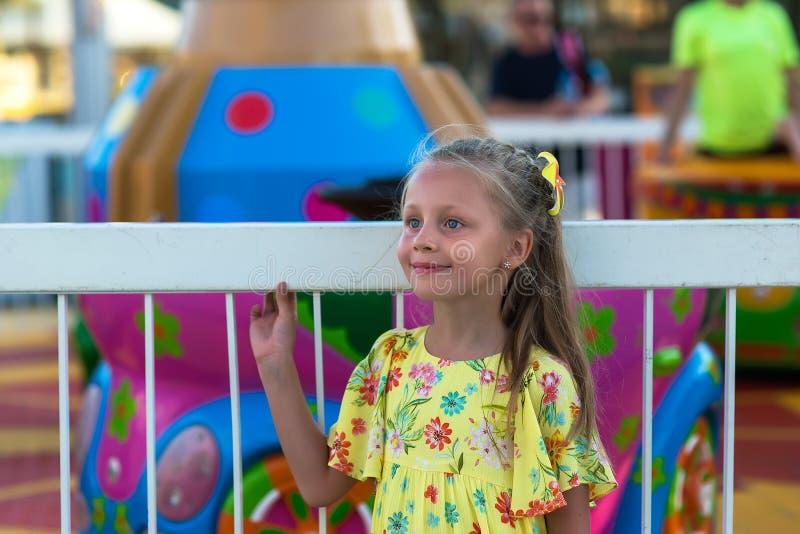 Närbildstående av att le flickan nära karusellen på mässan Stående av en gullig flicka på bakgrunden av ett nöjesfält arkivbilder
