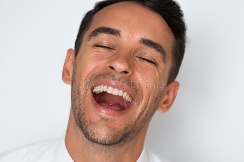 Närbildstående av attraktivt lyckligt skratta för man Isolerat på grå bakgrund Man med sunda tänder arkivbilder