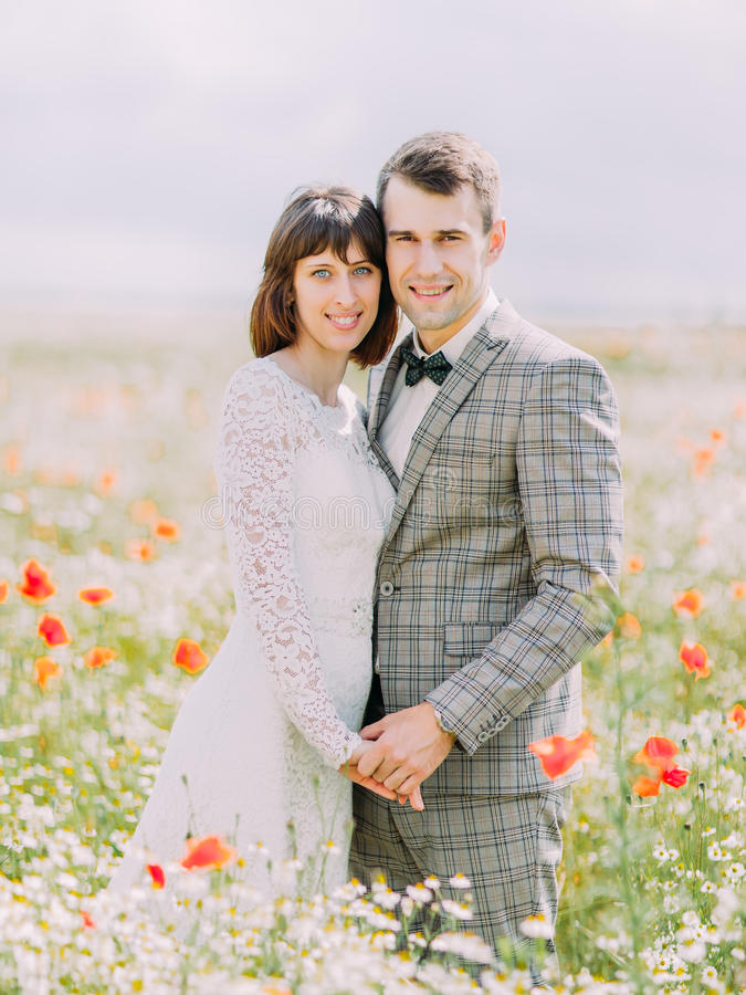 Närbildstående av de gladlynta nygifta personerna som rymmer händer och mycket kramar i fältet av blommor royaltyfri fotografi