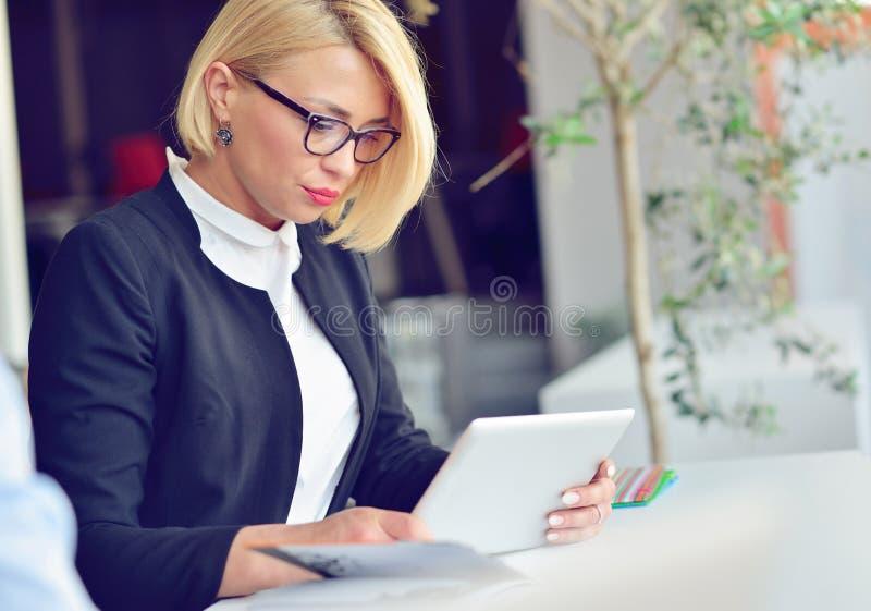 Närbildstående av den aktiva hållande bärbara datorn för affärskvinna, medan stå på kontoret royaltyfri fotografi