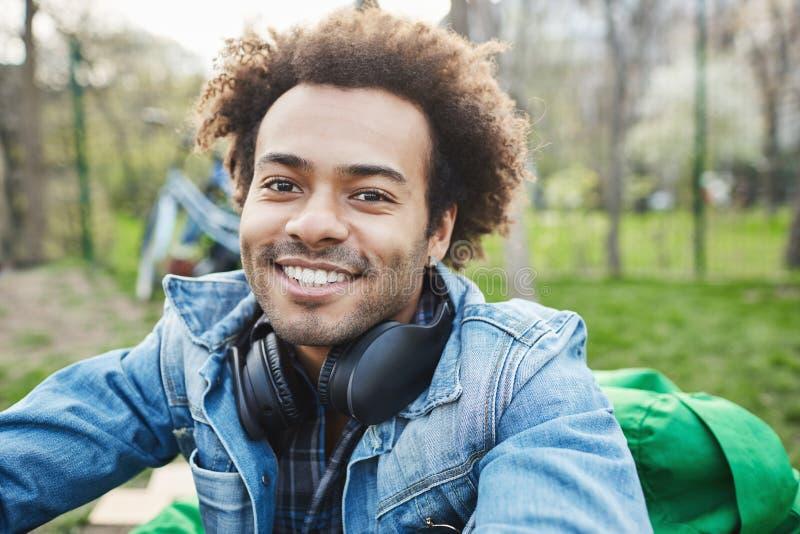 Närbildstående av den attraktiva orakade mörkhyade mannen med den afro frisyren som ler och uttrycker lycka medan arkivfoto