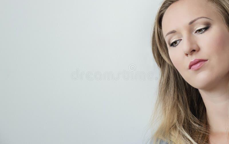 Närbildstående av den attraktiva unga härliga kvinnaframsidan som ner ser Nätt blond kvinna med gröna ögon fotografering för bildbyråer