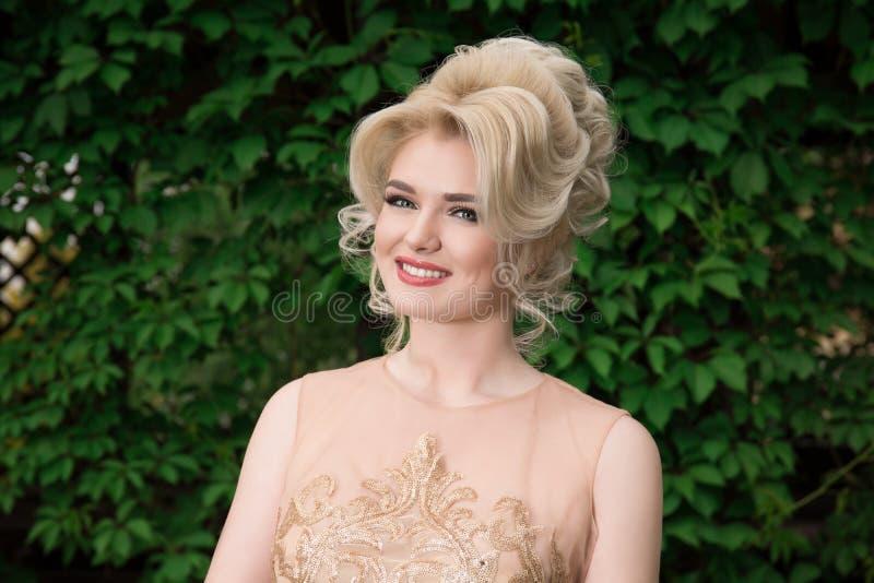 Närbildstående av den gulliga le kvinnan på en bakgrund av naturen som bär en beige klänning Se dig kamera Positiv framsida royaltyfri foto