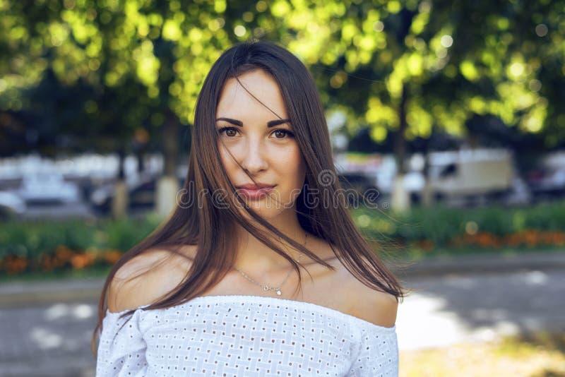 Närbildstående av den härliga brunettflickan som står i parkera, sommar, vit blus, långt hår, sinnlig blick, fotografering för bildbyråer