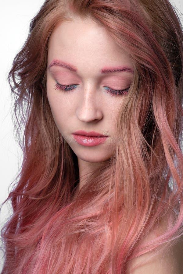 Närbildstående av den härliga flickan med rosa hår- och rosa färg-blått makeup som står med stängda ögon på en ljus bakgrund arkivfoton