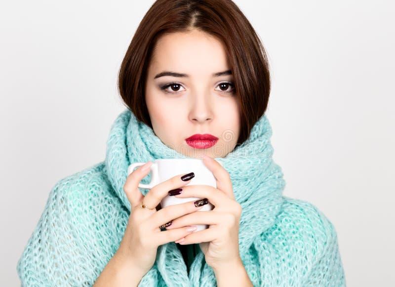 Närbildstående av den härliga kvinnan i en woolen halsduk och att dricka varmt te eller kaffe från den vita koppen fotografering för bildbyråer