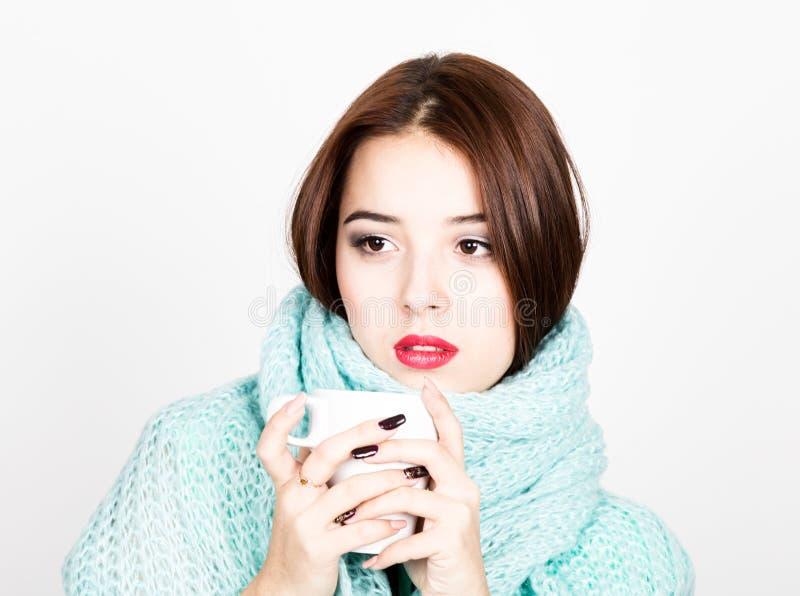 Närbildstående av den härliga kvinnan i en woolen halsduk och att dricka varmt te eller kaffe från den vita koppen arkivfoton