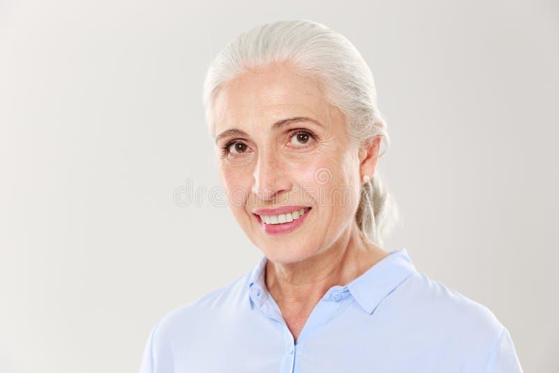 Närbildstående av den härliga le gamla kvinnan i blå skjorta, royaltyfria foton
