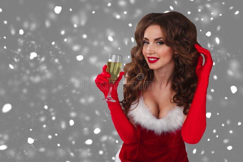 Närbildstående av den härliga sexiga kvinnan på den gråa bakgrunden med exponeringsglas av champagne och att se kameran arkivfoton
