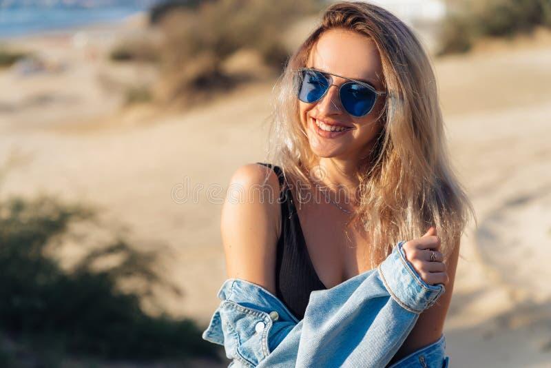 Närbildstående av den härliga smileing blonda modellen i svart baddräkt och solglasögon som poserar på stranden En flicka med a royaltyfria bilder