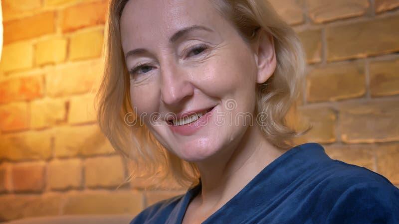 Närbildstående av den höga caucasian damen som lyckligt håller ögonen på in i kamera i hemtrevlig hem- atmosfär arkivbild