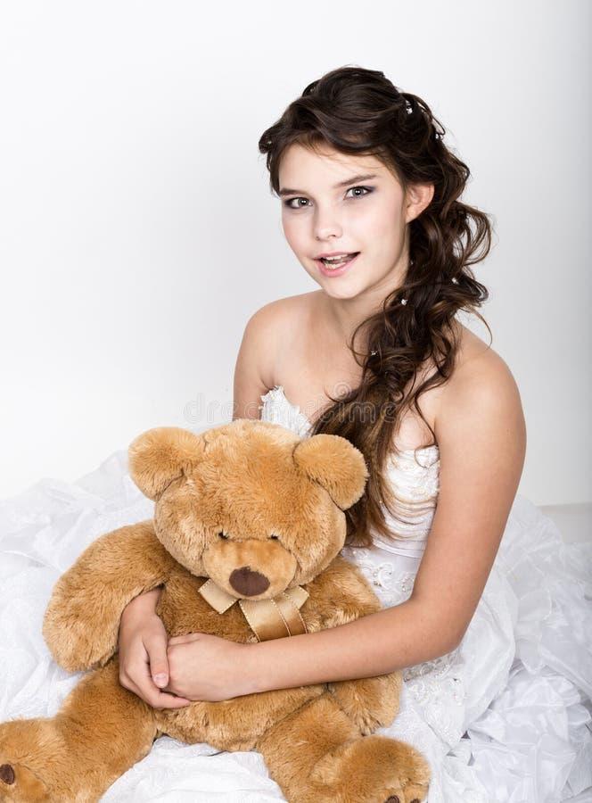 Närbildstående av den lockiga flickan som rymmer en nallebjörn fotografering för bildbyråer