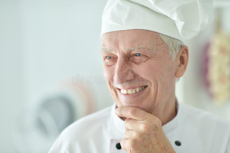 Närbildstående av den lyckliga äldre manliga kocken som hemma poserar royaltyfria bilder