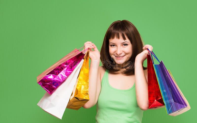Närbildstående av den lyckliga unga flickan med den färgrika shoppingpåsen royaltyfri foto