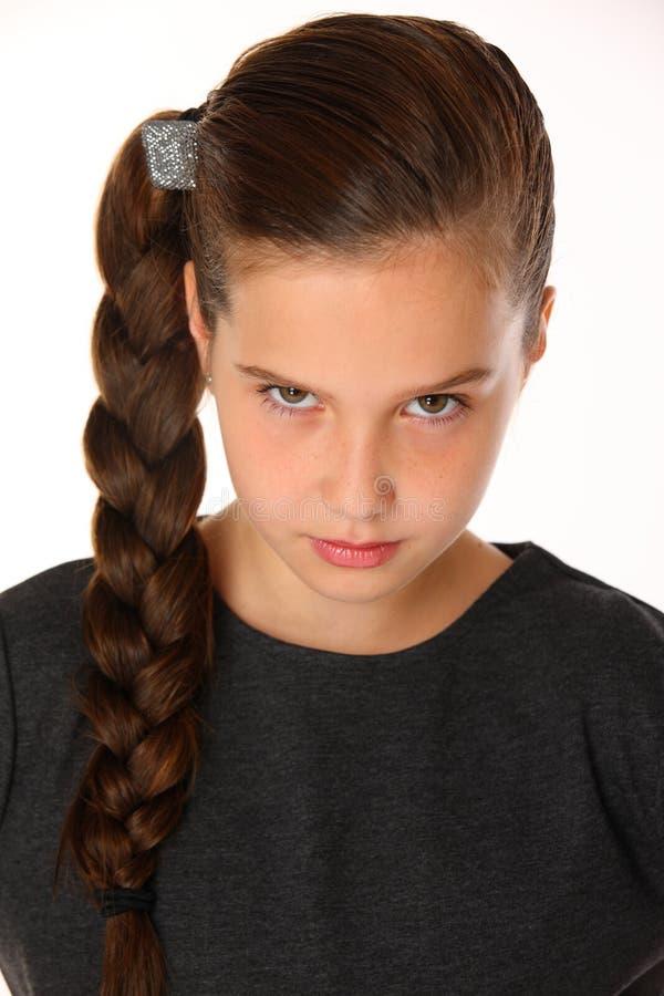 Närbildstående av den nätta unga skolflickan Hon är allvarlig och fordrande fotografering för bildbyråer