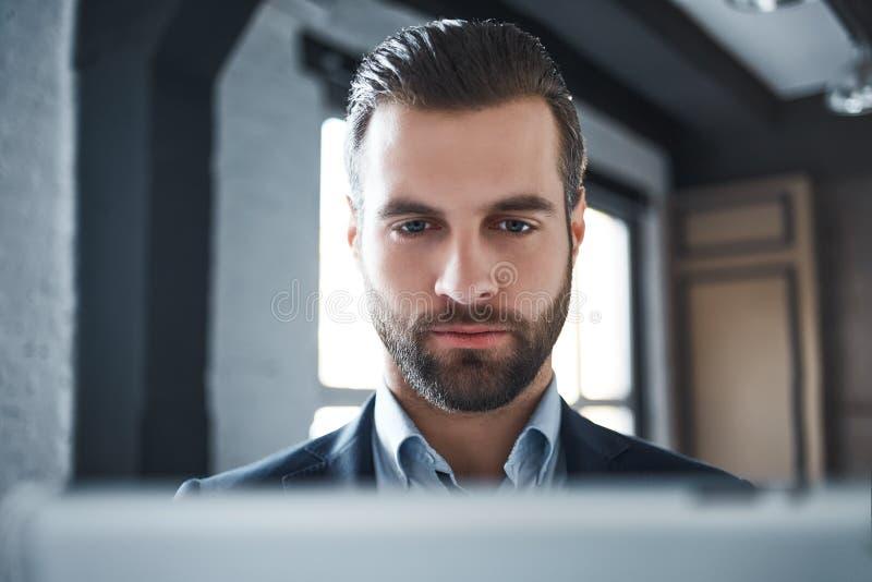 Närbildstående av den stiliga skäggiga mannen i en dräkt som allvarligt ser en kamera arkivbild