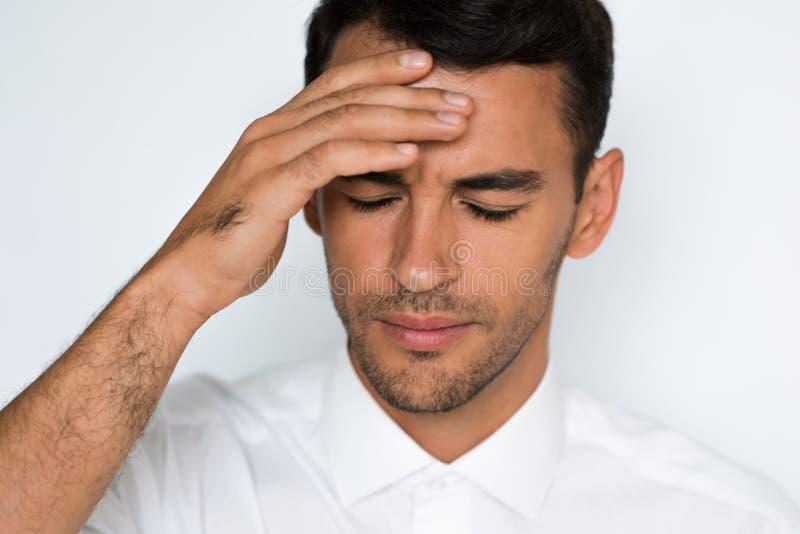 Närbildstående av den stressade stiliga handen för ung man på huvudet med dålig huvudvärk på vitt eller ljust - grå bakgrund arkivbilder