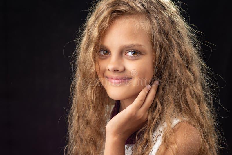 Närbildstående av den tonårs- flickan på svart bakgrund arkivfoton
