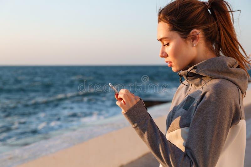 Närbildstående av den unga charmiga sportkvinnan som kontrollerar på nyheterna arkivfoton