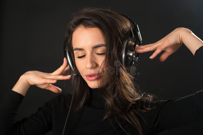 Närbildstående av den unga härliga brunettkvinnan som lyssnar till musik med hennes stängda ögon och över rymmer hörlurar royaltyfri foto