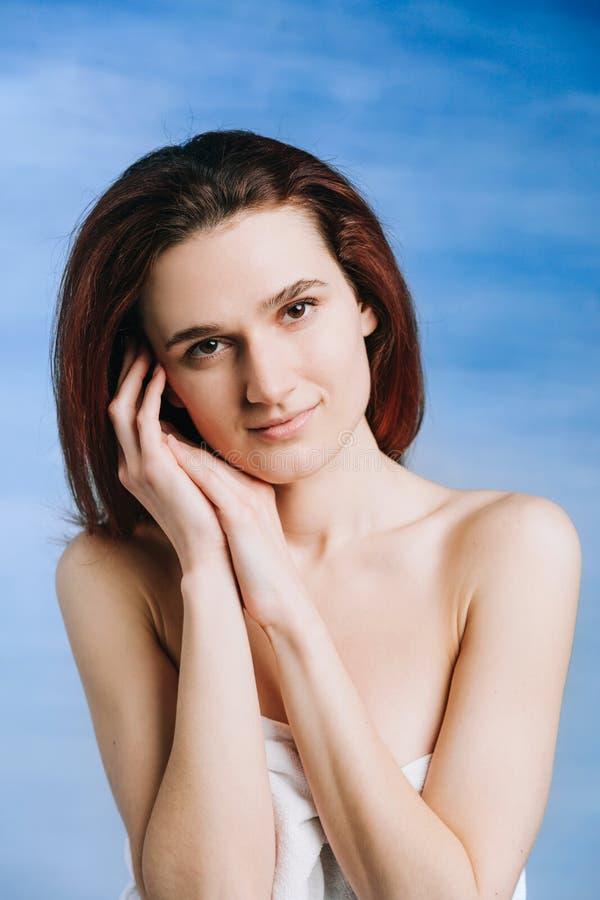 Närbildstående av den unga kvinnan med ren ny hud på en osminkad blå bakgrund gömma i handflatan av framsidan, arkivfoto