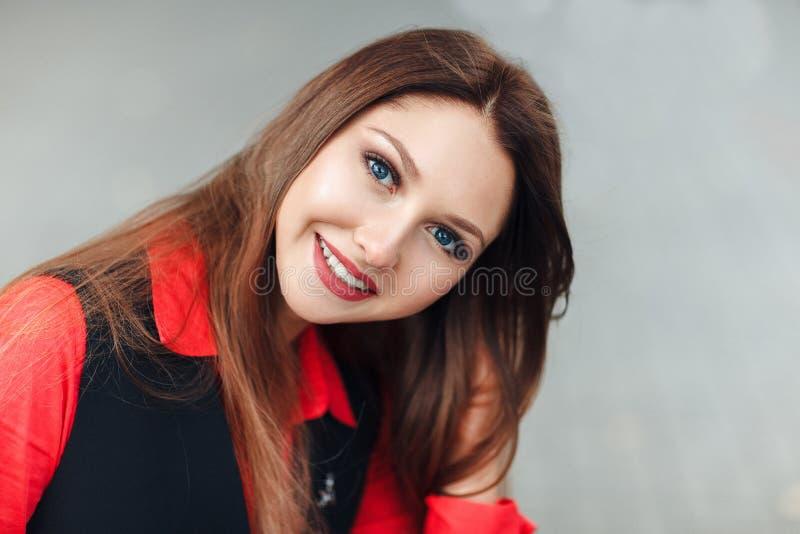 Närbildstående av den unga le kvinnan som ser kameran som ler Den attraktiva flickan med långt hårsammanträde kliver på en kasta  royaltyfri fotografi
