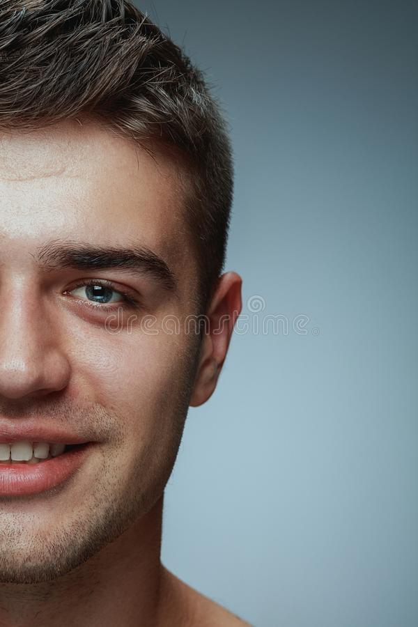 Närbildstående av den unga mannen som isoleras på grå studiobakgrund royaltyfri fotografi