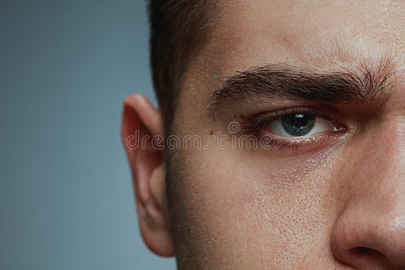 Närbildstående av den unga mannen som isoleras på grå studiobakgrund arkivbild