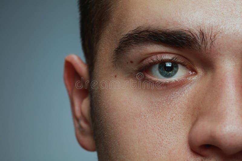 Närbildstående av den unga mannen som isoleras på grå studiobakgrund royaltyfria foton