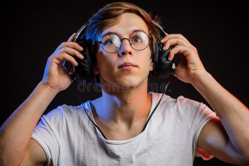 Närbildstående av den unga mannen som ser upp och sätter på hörlurar fotografering för bildbyråer