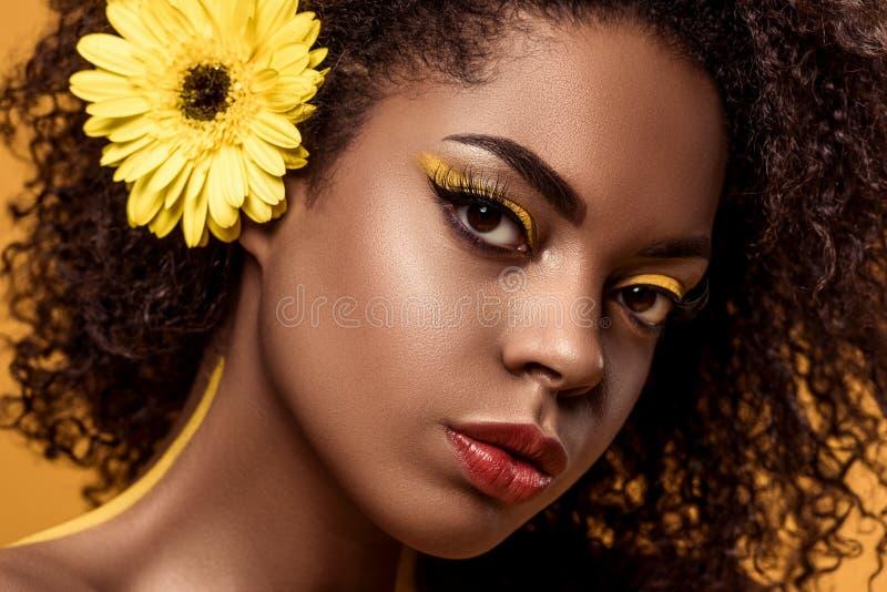 Närbildstående av den unga sinnliga afrikansk amerikankvinnan med konstnärligt smink och gerberaen i hår royaltyfri fotografi