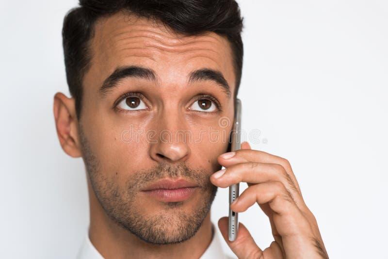 Närbildstående av den unga stiliga mannen som använder mobiltelefonen på grå bakgrund Affärsman som talar på hans smarta telefon royaltyfri foto