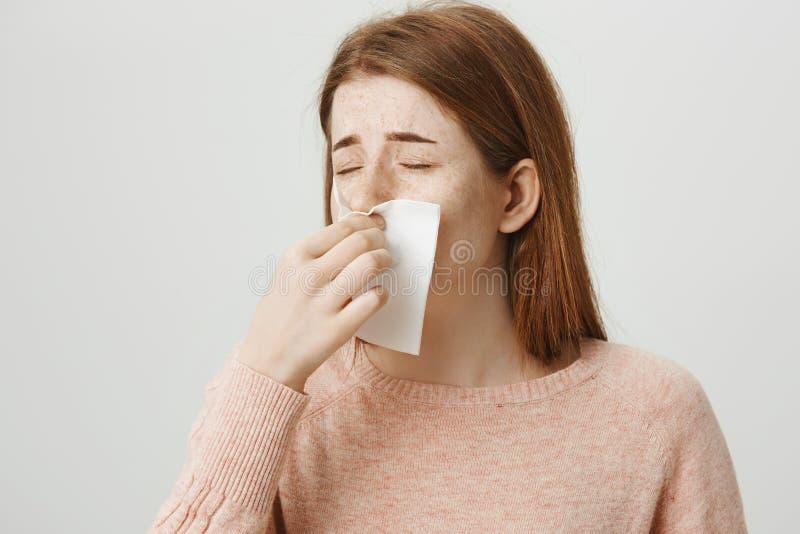 Närbildstående av den upprivna rödhårig manflickan som har förkylning eller influensa som blåser näsan i servett, medan rynka pan royaltyfri fotografi
